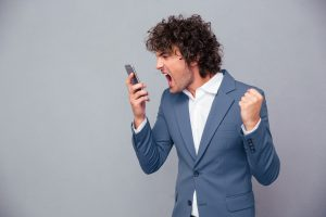 Portrait of angry businessman shouting on smartphone over gray background